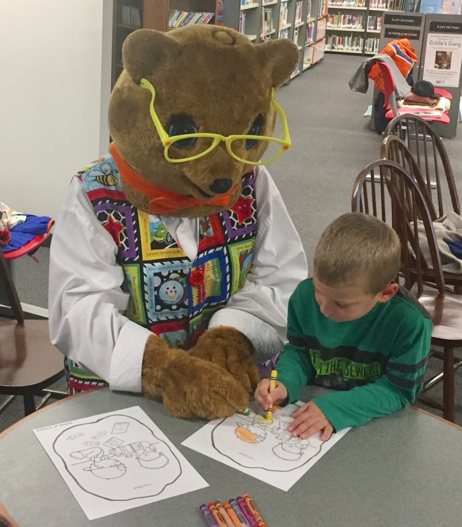 Kody O'Bear helping a student with his coloring project. Reading with Kody O'Bear Class. Milton Public Library, Milton, Delaware. January 2020